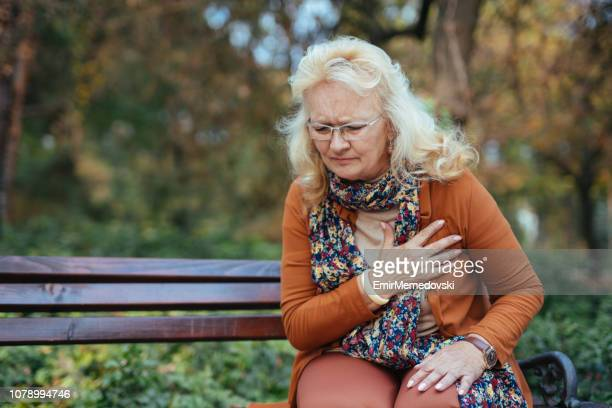 elderly woman having chest pains or heart attack in the park - heart disease stock pictures, royalty-free photos & images