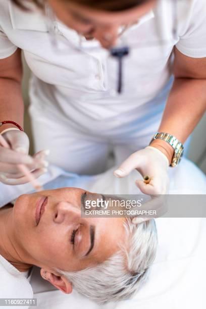 年長的女人,她的眉毛由美容院的專業美容師塑造 - 修眉 個照片及圖片檔