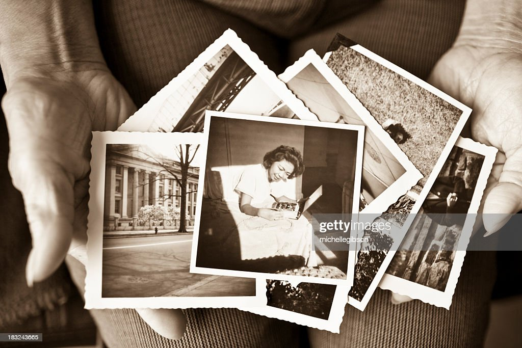 Elderly woman holding a collection of old photographs : Stock Photo