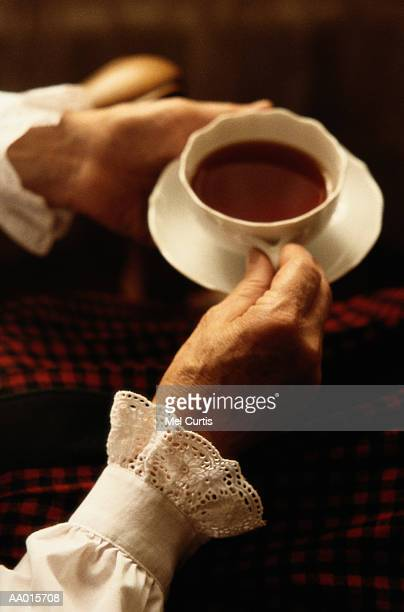 elderly woman holding a cup of tea - lace blouse stock pictures, royalty-free photos & images
