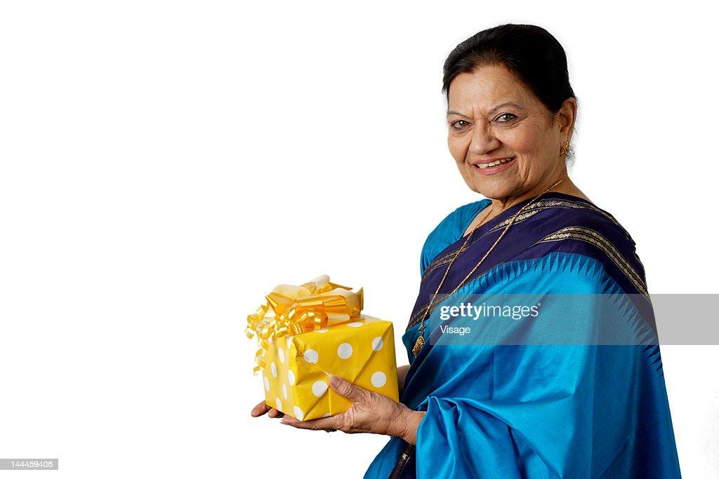 Elderly woman holding a gift box : Stock Photo