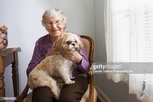elderly woman holding dog - um animal imagens e fotografias de stock