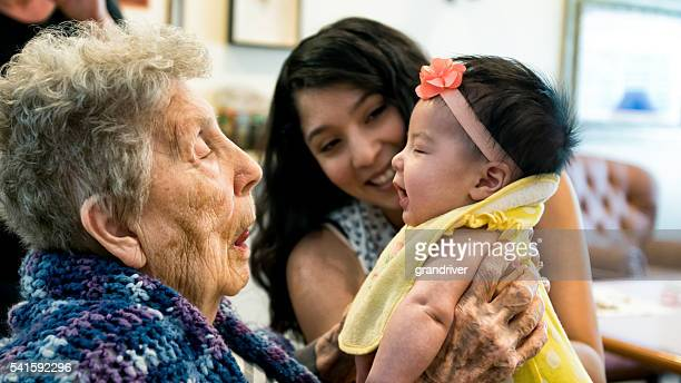 elderly woman holding infant granddaughter as mother looks on smiling - baby human age stock pictures, royalty-free photos & images