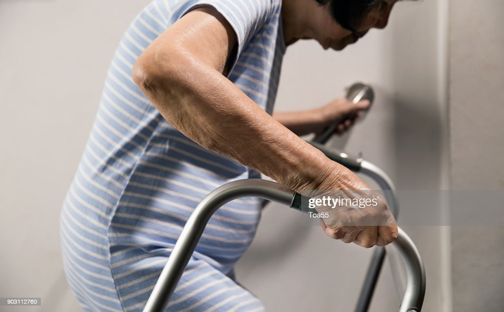 Elderly woman holding on handrail and walker for safety walk steps : Stock Photo