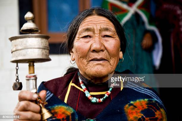 Elderly woman holding prayer wheel
