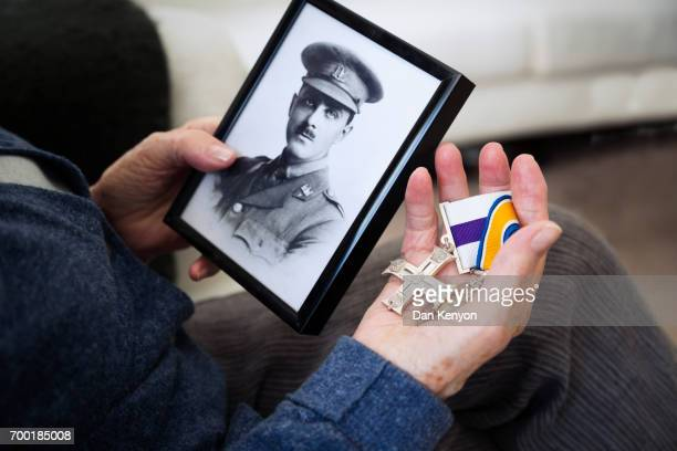 Elderly woman holding WW1 medals and photograph of soldier