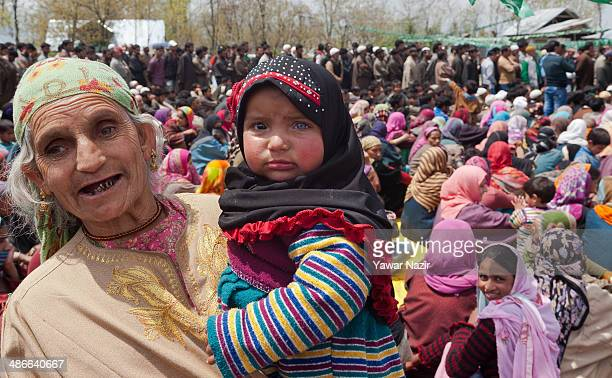 A elderly woman holds a baby with Heterochromia of the eye as she listens to Muzaffar Hussain Beigh Kashmir's former deputy chief minister and a...