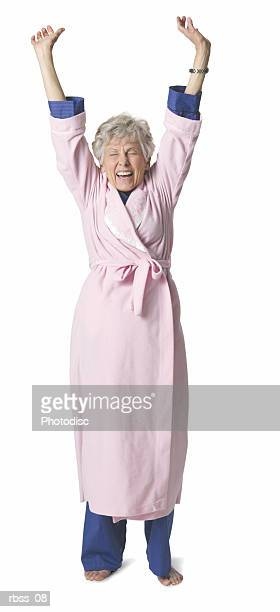 Elderly woman in a bathrobe stretches.