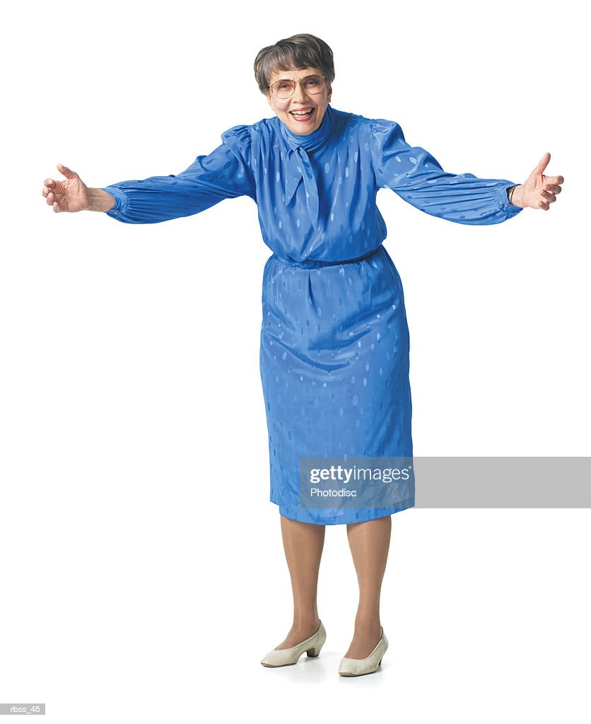Elderly woman in a blue dress smiles reaching out. : Foto de stock