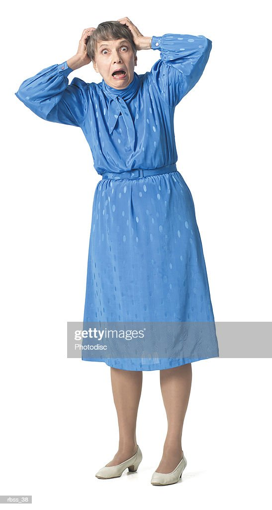 Elderly woman in a blue dress stares at the camera with a scared look on her face. : Foto de stock