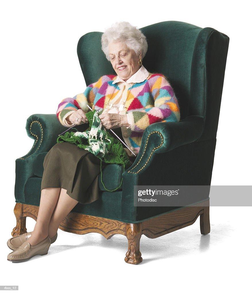 Elderly woman in a colorful sweater knits. : Foto de stock