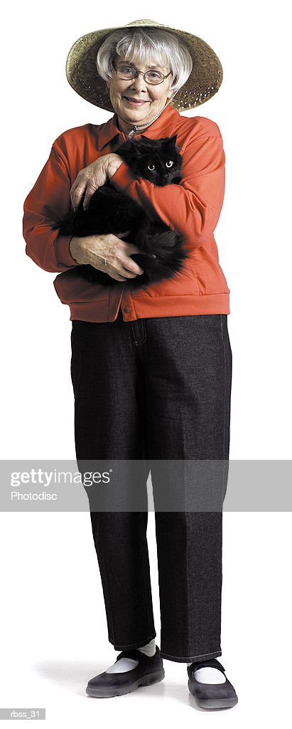Elderly woman in a red shirt and a straw hat smiling at the camera holding a cat : Foto de stock