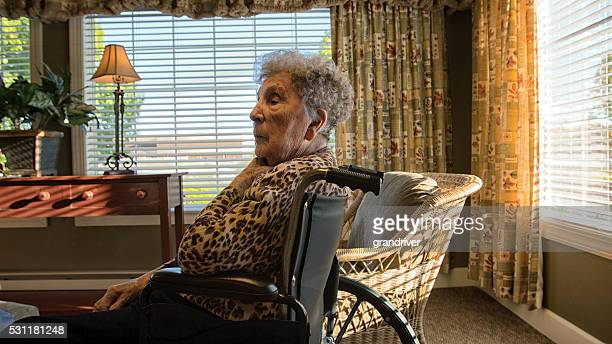 Elderly Woman In A Room With Windows And A Chair.