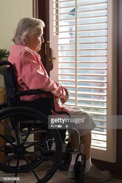 Ältere Frau im Rollstuhl mit Blick aus dem Fenster