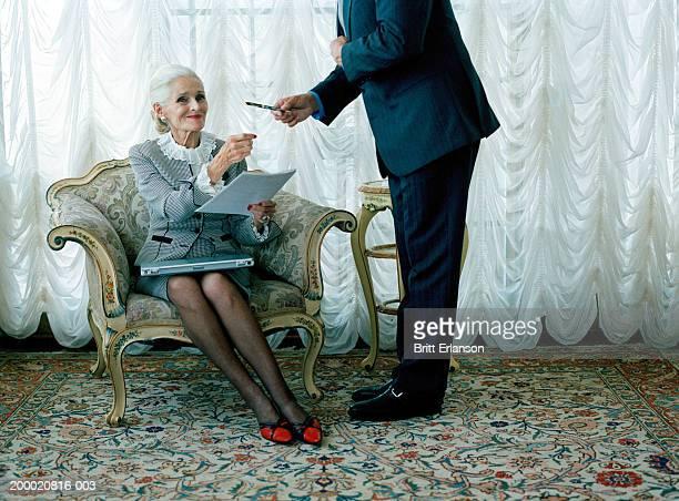 Elderly woman in chair being handed pen by man, portrait