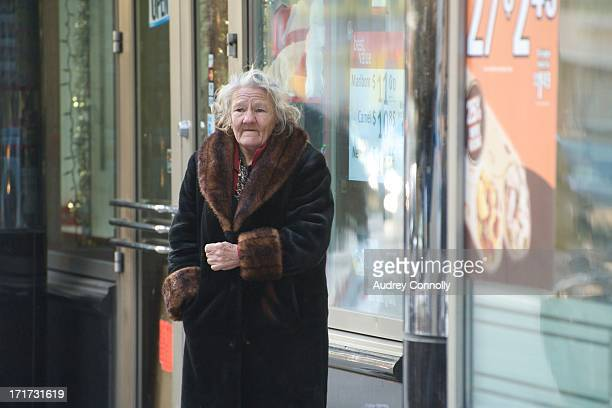 Elderly woman in coat outside convenience store in midtown Manhattan, New York City