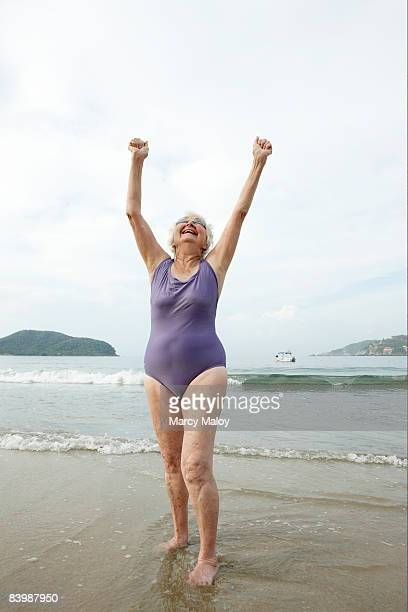Elderly woman in swimsuit & goggles stretching.