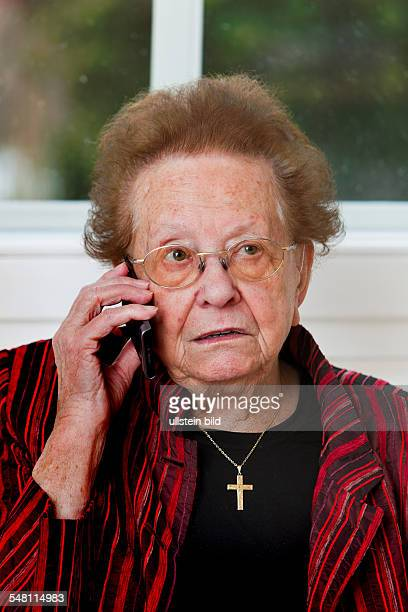 elderly woman is having a phone call with mobile phone