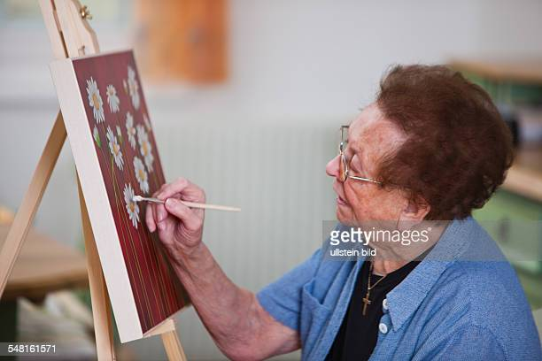 Elderly woman is painting a picture -