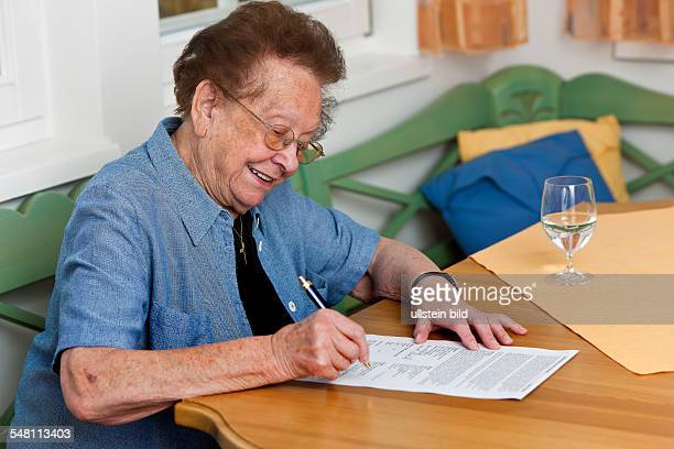 elderly woman is signing a contract