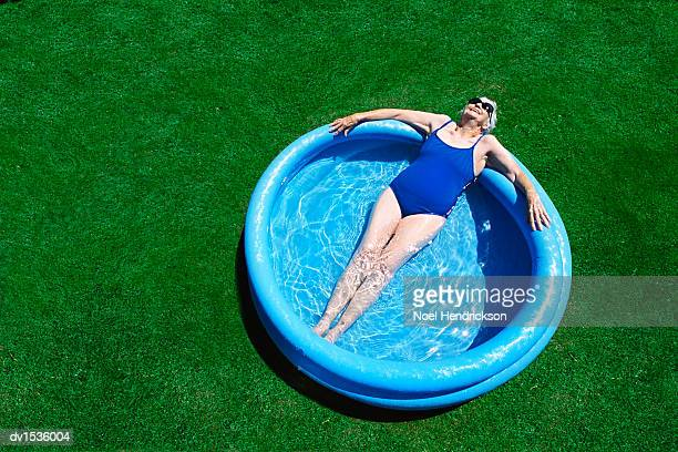 Elderly Woman Lies in a Blue Paddling Pool, Sunbathing and Relaxing