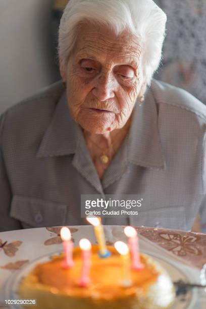 Elderly woman looking at birthday candles with melancholic expression