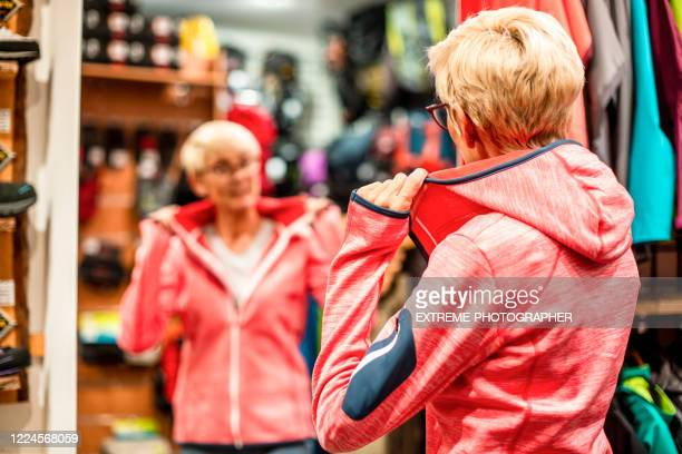 elderly woman looking at herself in a mirror while trying on a sports jacket in a sports equipment shop - sports equipment stock pictures, royalty-free photos & images