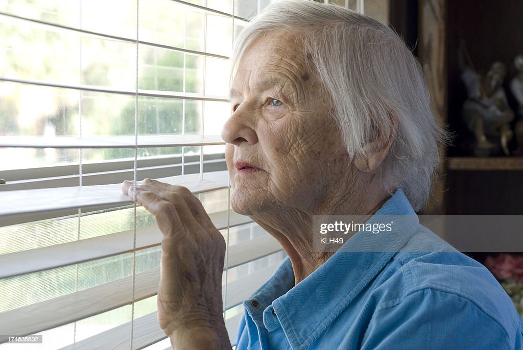 Elderly woman looking out a window. : Stock Photo