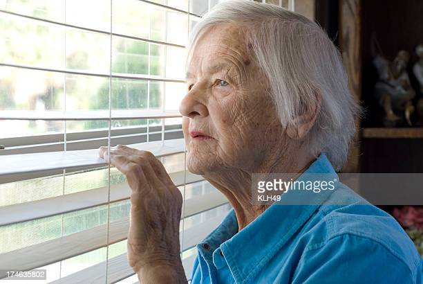 Elderly woman looking out a window.