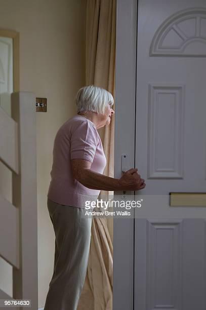 Elderly woman looking out of the door of her home