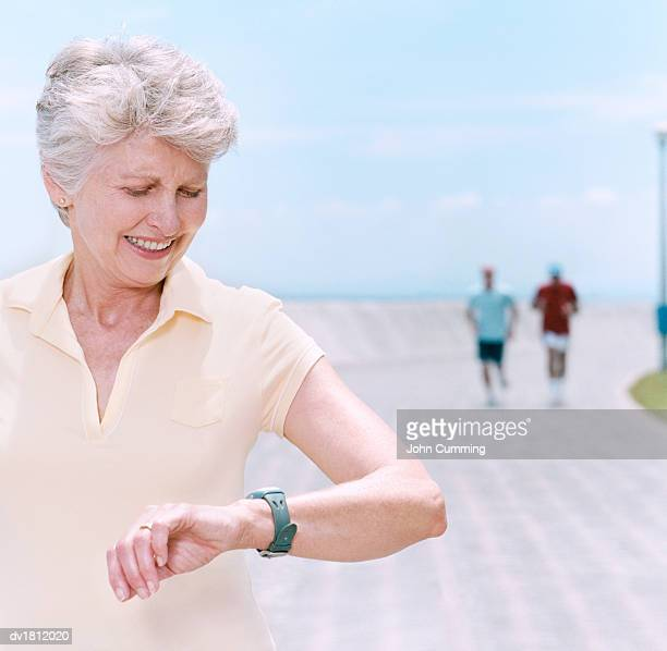 Elderly Woman on an Athletics Track Timing Herself With Her Watch