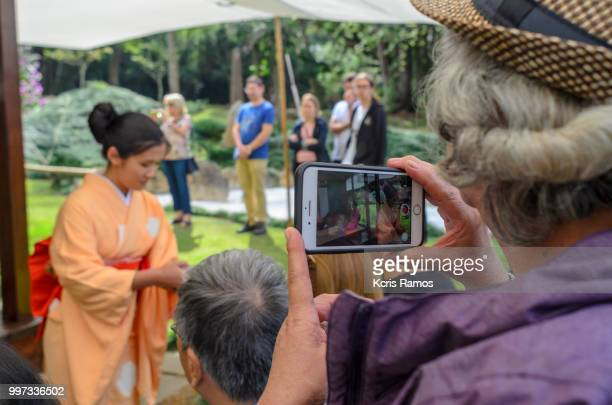 elderly woman on the back photographing with cellular tea ceremony at the public cherry festival on a clear day on July 7, 2018 in fetival Sakura matsuri, Sao Roque, Sao Paulo, Brazil