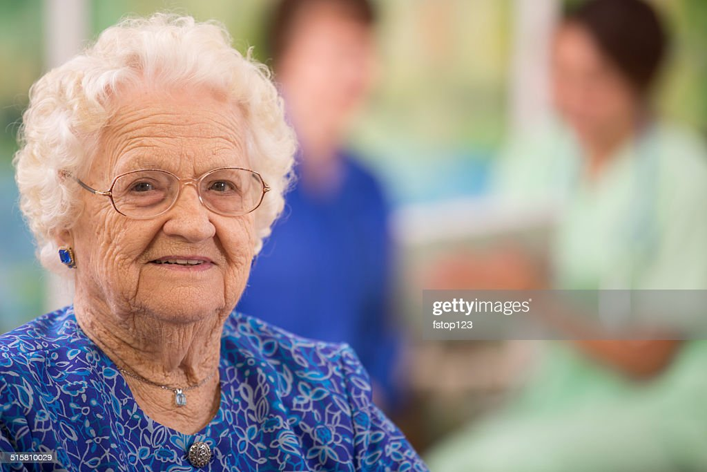 Elderly woman patient foreground. Nurse, daughter. Nursing home. : Stock Photo