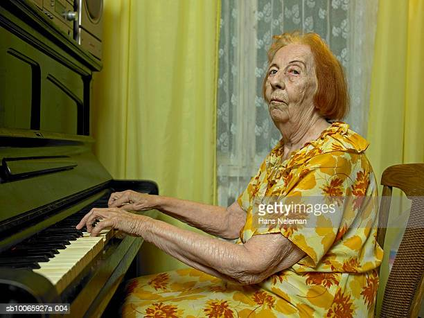 elderly woman playing piano - piano key stock photos and pictures