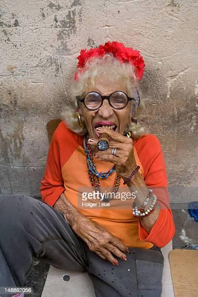 Elderly woman posing with Cuban cigar.