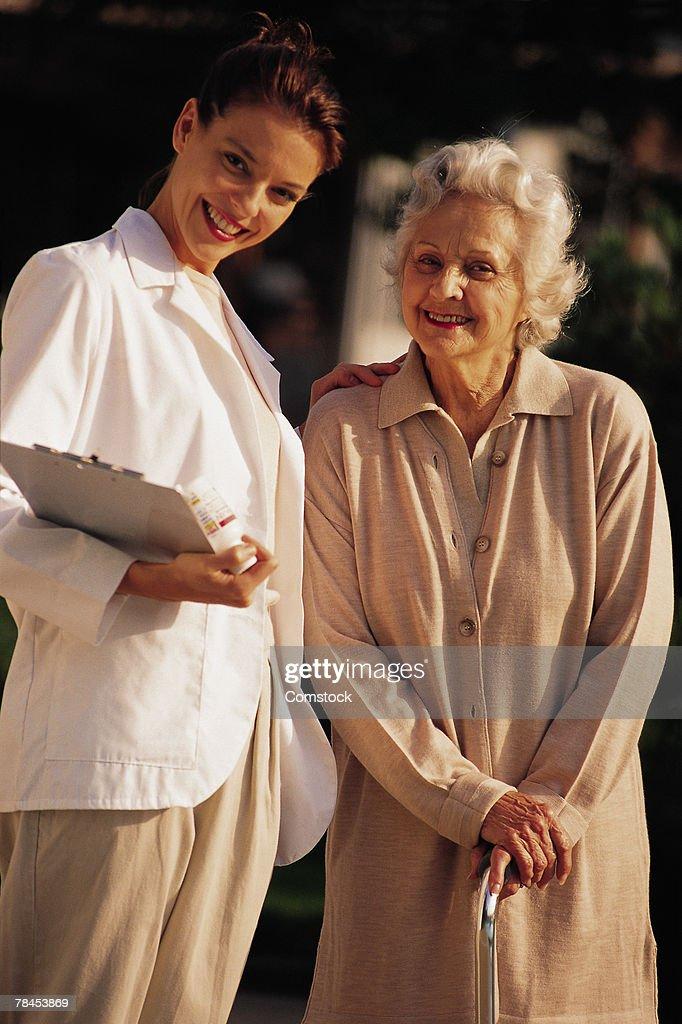Elderly woman posing with nurse outdoors : Stockfoto