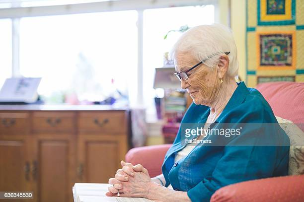 Elderly woman praying and reading the bible