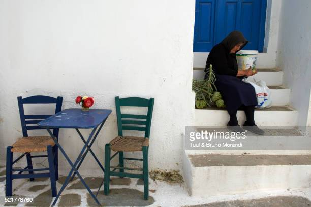 Elderly woman preparing food on steps, Langada village, Katapola bay, Amorgos, Cyclades islands, Greece