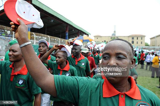 Elderly woman raises her cap as workers march to salute Lagos State Governor Babatunde Fashola during a workers rally to mark May Day in Lagos on May...