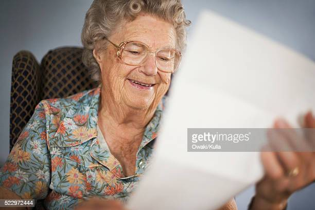 elderly woman reading a letter - one senior woman only stock pictures, royalty-free photos & images