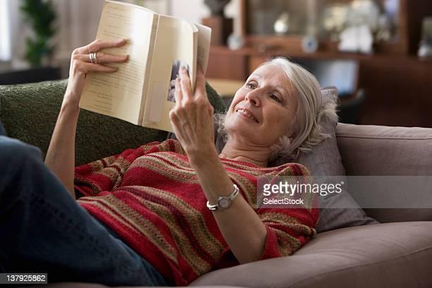 Ältere Frau liest ein Buch auf dem sofa