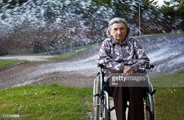 Elderly Woman Relaxing by the Fountain in a Park