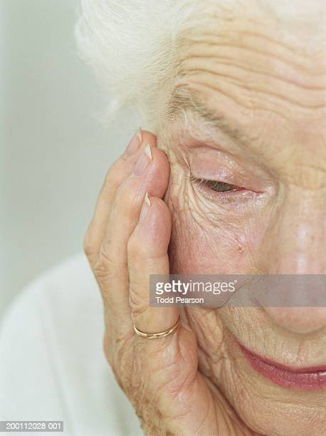 Elderly woman resting chin in hand, close-up