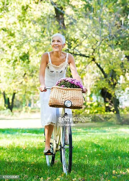 elderly woman riding a bicycle in a park - grey dress stock pictures, royalty-free photos & images