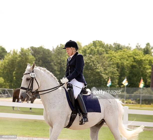 elderly woman riding a dressage course - riding crop stock photos and pictures