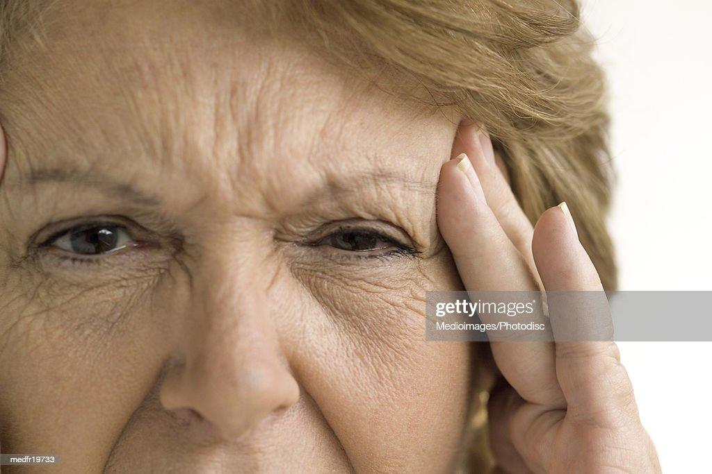 Elderly woman rubbing her temple : Stock Photo