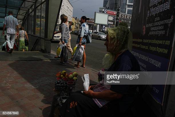 Elderly woman sells the homegrown fruits in downtown Kyiv