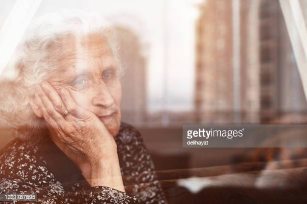 elderly woman sitting alone and looking sadly outside the window - loneliness stock pictures, royalty-free photos & images