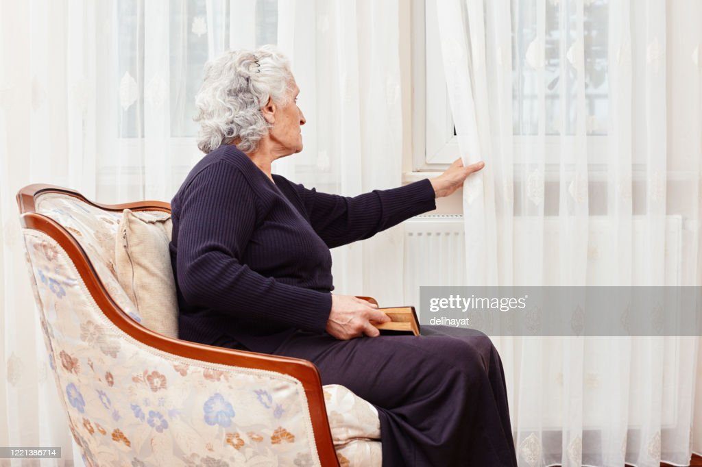 Elderly woman sitting alone with a book in hand and looks sadly outside the window : Stock Photo