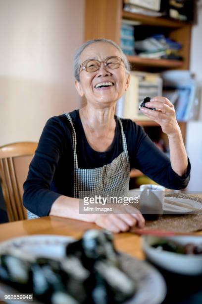 elderly woman sitting at kitchen table, eating sushi, smiling at camera. - smiling ストックフォトと画像